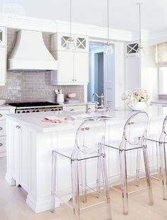 So in love with this kitchen! I love the white kitchen cabinets, commercial grade gas range, and X's on the glass upper cabinets. Gray glass backsplash and light hardwood floors.