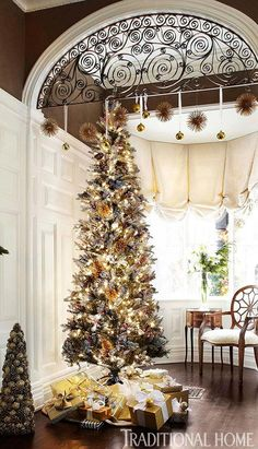 Like the high ceilings with the iron work arch.  The white panelling/dark upper ceilings and detailed high moldings are beautiful.   Decorating: Christmas Trees - Traditional Home®