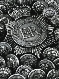 The making of Greater Manchester Police.    An early – pre enamel – helmet plate of Greater Manchester Police lies surrounded by tunic buttons of some of the forces amalgamated to form GMP, or who gave up some of their area to the Force on its creation in 1974.    This image was created by one of the Force's photographers using objects from the collection of the Greater Manchester Police Museum.    http://www.gmpmuseum.com