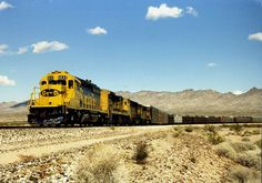 Out in the Mojave - A Santa Fe auto train (with open racks!) curves through the desert west of Needles in 1989. SD40-2s and a C30-7 provide the classic Santa Fe locomotion.