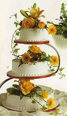 A wedding cake decorated by flowers and interesting foliage. The floral bouquet is made up of yellow roses, yellow germinis and yellow lillies, arranged by a proffesional florist from Elsie Russell Florist, Shipley Wedding Cake Display, Wedding Cake Decorations, Wedding Cake Roses, Elegant Wedding Cakes, Pretty Cakes, Beautiful Cakes, Cake Pedestal, Just Cakes, Creative Cakes
