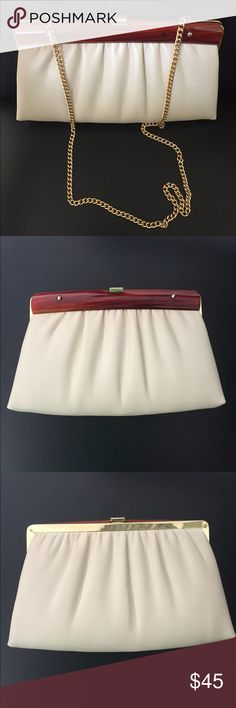 """Vintage Cream & Lucite Clutch or Crossbody Bag Super classy cream colored Clutch or Crossbody Bag has gold-tone hardware & a fabulous Lucite tortoise shell top accent. Clicks closed at the top. Inside lined in matching fabric (tiny spot inside as shown). All sides shown. This purse fits easily in your hand as a clutch or you can choose to tuck the chain inside and it hangs readily by your side.  Measures 10"""" wide x 6"""" tall (add 14"""" for chain drop). In excellent preowned condition. Smoke-free…"""