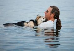 A photo of John Unger holding his shepherd mix in a lake as the dog sleeps has gone viral, the image portraying the incredible bond between man and dog.