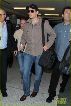 09 June 2013 : Henry Cavill flashes a smile as he heads through LAX on Sun(Jun 9) .