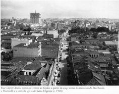 1928 - Rua Casper Líbero rumo ao centro da cidade. Ao fundo, a partir da esquerda, as torres do Mosteiro de São Bento, o edifício Martinelli e a torre da igreja de Santa Ifigênia. Foto de autoria desconhecida. Acervo do Instituto Moreira Salles.