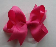 hair bow made from grosgrain ribbon (l.5 wide) and attached to a partially covered alligator clip. Approx. 4 inches across. Ribbon ends have been heat sealed to prevent fraying.