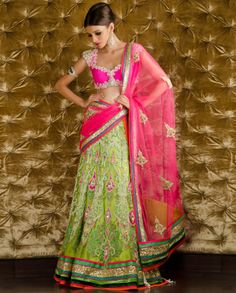 Embellished Hot Pink and Parrot Green Lengha Choli: Parrot green ornately embellished lengha with matching satin lining. Faux pearl baby bead embellished applique work adorn the lengha with golden sequined border. The set also include hot pink raw silk padded choli with crystal and rhinestone embellishments at center. Faux pearl baby bead embellished swirl designs adorn the neckline and sleeves. Faux pearl baby bead, golden bugle bead embellished applique adorn the net dupatta - PAM MEHTA