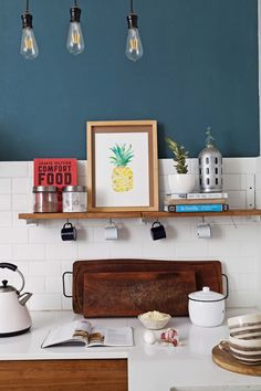 """En esta cocina joven, el color petróleo eleva y proyecta la pared de la alsada de la mesada, y combina perfecto con los azulejos tipo """"Subway"""" en blanco."""