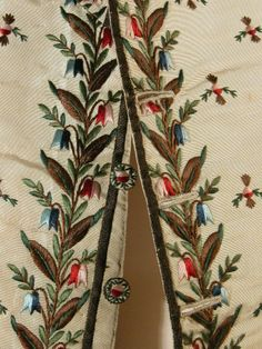 Detail embroidery, waistcoat, c. 1760-1770. Cream corded silk embroidered in blue, green, brown, red and pink with borders, pocket flaps and all-over sprig embroidery.