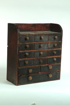 "DIMINUTIVE CASE OF DRAWERS.  American, 19th century, mixed woods. With twelve small drawers over three larger drawers, and a dark finish. 23""h. 20.5""w. 8.5""d."