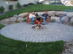 Timber Creek Landscape - Edina, MN, United States. Boulder retaining wall with firepit in paver circle.