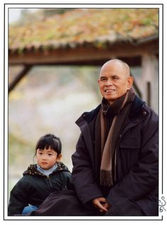 Thich Nhat Hanh sitting with little Mylinh Pham in the Lower Hamlet, Plum Village.