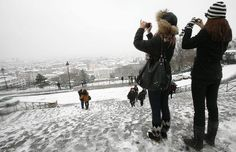 Tourists take pictures of the Eiffel Tower, Sacre Coeur, Montmartre, Tulieries   gardens, Arc de Triomphe and Notre-Dame cathedral in the snow.