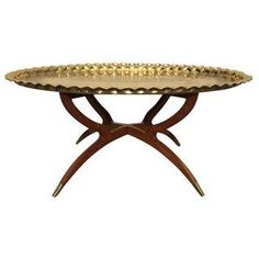 Beautiful Mid-Century Modern round brass tray top cocktail table. From the 1950s - 1960s. This stunning tray table is mounted on a wooden base with a spider leg design, each foot being decorated with a brass tipped cap.