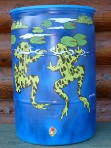 Two frogs painted on outside of rain barrel.