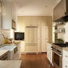 honed seagrass limestone counters, steel shelves flanking oven, apron sink, subway tile, elongating cabinets = making the most of a narrow kitchen