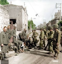 US soldiers of the 41st Armoured Infantry Battalion, US 2nd Armoured Division, guard German POWs at the entrance to Rue des Fossés Plisson, in Domfront, Lower Normandy, France.