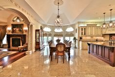 I love the transition from the kitchen to the family room; columns, archway, and level flush floors going from stone tile to hardwood. Also the different colour wood for the kitchen island, and the different ceiling heights.
