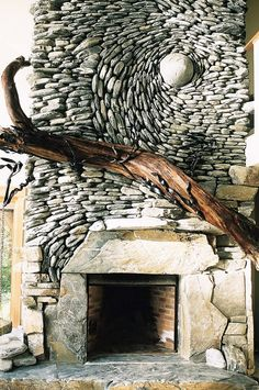 Stone mosaic fireplace with raw wooden detail.