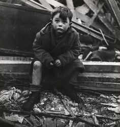 Child sitting in the rubble of his home where his parents lie buried after a V-2 bomb hit, London, January 1945. Sad