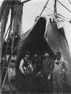 Whaling ship crewmen pose beneath baleen