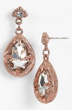 Gorgeous rose gold earrings with pear shaped diamonds, accent diamonds, and unique prongs holding the gems in place.