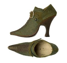 Zapatos— Shoes decorated with green tape application, silk gros ligament Naples, 1730. The blade is high, trapezoidal shaped ear and toe is very pronounced. They close with two nails rectangular buckle, enriched by crystals mimicking old-cut diamonds, set with four claws. The heel is very high, and the soles are leather and are stitched in white cotton thread. Museo del Traje  © Ministerio de Educación, Cultura y Deporte