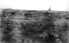 Circa 1900 - Looking toward the west side of the United States Capitol building, a panoramic view of the city of Washington, D.C. shows the Mall area in the foreground before the railroad tracks were removed. A train is visible on the tracks. The domed structure in front of the Capitol is the Botanic Garden original octagonal greenhouse of 1859 and behind it the central pavilion added after the Civil War.