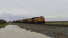 https://flic.kr/p/Qr3Dez | Pulling and Pushing | The DPU of a westbound freight can be seen in the distance pushing away from the 6 engines at the lead of an eastbound train accelerating out of Stockton on this rainy afternoon in the central valley.