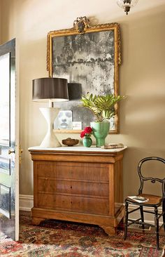 "The marble-topped antique chest in the foyer was purchased at a French flea market. Wall paint (""Oak Flats"" #8684) and trim paint (""Shell White,"" by Duron), both discontinued, can be mixed by Sherwin-Williams);  Ceramic plant holder: Two's Company,   ""Julian Mirror"" #50-04593-4160): Niermann Weeks."