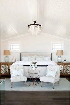 Gorgeous bedroom, rustic wood floors, bead board ceiling, white wall, beige chairs, white duvet   Becki Owens