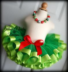 PLEASE CHECK MY SHOP ANNOUNCEMENT FOR CURRENT TURN AROUND TIME! RUSH ORDERS ARE AVAILABLE FOR AN EXTRA FEE. Your little cutie will be ready for the holiday festivities in this super cute tutu! Perfect for birthday parties, pageants, Halloween costumes, photo shoots and more! Emerald green tutu with lime green ribbon trim and a red Bow. Non roll elastic waistband. Skirt can be worn so that the bow is on the front or in the back. WAIST Size: Newborn: 14 0-3m: 15 3-6m: 16 6-9m: 18 9-18m: 19 ...