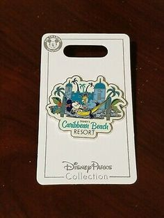 Open edition release for Disney's Caribbean Beach Club Resort pin released in 2018. Pin featuring Mickey Mouse in a yellow hammock drinking from a pineapple with towers and palm trees from the resort behind him in teal and blue.