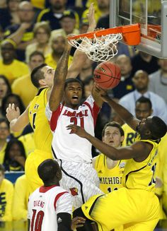 Louisville Cardinals forward Chane Behanan (C) dunks the ball between Michigan Wolverines forward Mitch McGary (L) and guard Tim Hardaway Jr. (R) in their NCAA men's Final Four championship basketball game in Atlanta, Georgia April 8, 2013. REUTERS/Tami Chappell