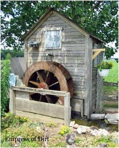 Water wheel on the shed... add a pond and it's perfect!