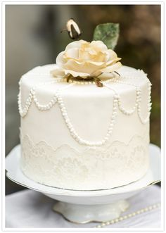 white cake with lace and pearl-like details