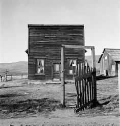Dorothea Lange. A gate with no fence. A house that doesn't look like a house.
