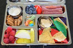 Yogurt, chocolate chip thinsations, raspberries, pears, tortilla chips, hummus, german salami, babybel cheese, blueberries, candy