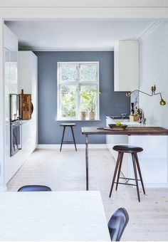 Nordic and stylish kitchen from Multiform with marble, raw wood and characteristic wall lamps.