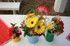 Gerberas and bear grass with pale pink chrysanthemums in multi coloured tins