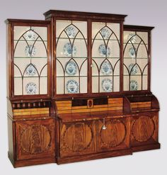 """A magnificent, unusual George III period mahogany Breakfront Bookcase having a moulded cornice & Gothic arch astragal glazed doors above 3 ebony inlaid cylinder secretaires fitted with various satinwood drawers & pigeon holes, the central cylinder with pullout writing slide. The Bookcase with unusual """"stop fluted"""" column corners having 4 mitred doors with rosewood crossbanded flamed-figured circular panels, raised on plinth base. Circa: 1800 Ref: 5466"""