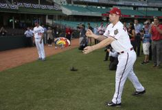 The Arizona Diamondbacks' Paul Goldschmidt, right, passes a rugby league football at the Sydney Cricket Ground in Sydney, Wednesday, March 19, 2014. The MLB season-opening two-game series between the Dodgers and Diamondbacks in Sydney will be played this weekend. (AP Photo/Rick Rycroft)