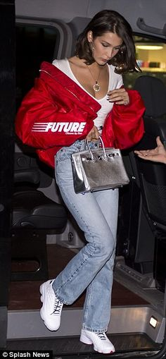 Toned: Meanwhile, Bella displayed her toned abs in a white crop top, over which she slung a red padded jacket, teamed with boot cut faded jeans and crisp white sneakers