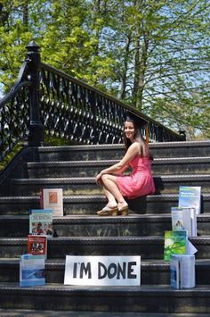 Nursing graduate celebrating and displaying her books. Maybe now she can read some novels.