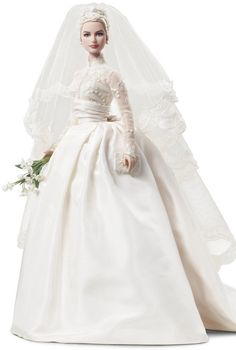"""The Grace Kelly bride doll wears a long-sleeve lace wedding gown reminiscent of the one the princess wore. She wears a delicate headpiece and veil, and holds a bouquet of white flowers and a prayer book, as Kelly did when she exchanged vows with Prince Rainier III in 1956."""