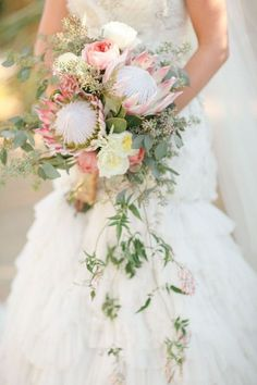 Top 10 Unique Bridal Bouquets - Project Wedding | A pair of king proteas, clusters of seeded eucalyptus and cascading greens make for a romantic, exotic look.