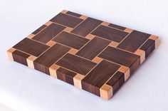 This chopping board is made using endgrain maple and walnut - great for your knives, and beautiful too. Construction is very strong and durable, and the finish is a foodsafe natural oil that repels water and stains. This serving and display board would be a fine background for cheese or charcuterie. It combines a basketweave pattern with Celtic knot shadows. All of the walnut pieces come from the same board for grain consistency. The pieces are then arranged to produce a harmonious…