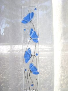 Cobalt blue transparent glass I chose for the flowers. I placed them on clear glass, and painted the stems with glass enamel paint. I then fired it in my kiln for a day to 1300 degrees. It measures 10 x 2. It looks great hung in a window with light coming through and comes with the