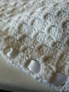 Hand-crocheted, corner-to-corner, baby afghan with white ribbon border.