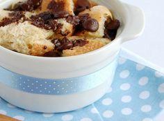 Receita de Pudim de Pão com Gotas de Chocolate - 250g de pão amanhecido, em cubinhos de 2,5cm (aprox. 5 1/2 xícaras de cubos), 1/2 xícara (92g) de gotas de chocolate amargo, 3 ovos, 3 colheres (sopa) de açúcar mascavo claro – aperte-o na colher na hora de medir, 2 colheres (sopa) de rum escuro, 1/2 xícara (120ml) de creme de leite fresco, 2 xícaras (480ml) de leite integral, 4 colheres (chá) de açúcar demerara